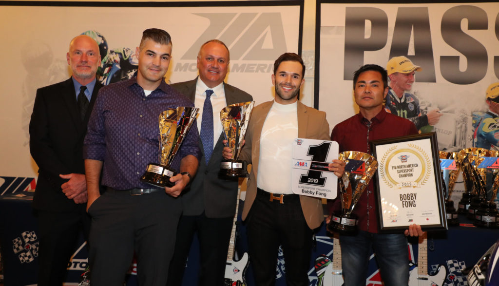 (From left to right) Massey, team manager Chris Ulrich, MotoAmerica Partner Chuck Aksland, Bobby Fong and crew chief Frank Aragaki help Fong with his Supersport Championship hardware. Photo by Brian J. Nelson.