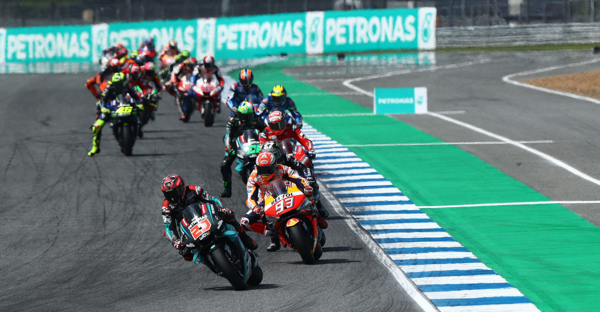 Fabio Quartararo (20) leads Marc Marquez (93) and the rest of the field early in the MotoGP race in Thailand in 2019. Photo courtesy of PETRONAS Yamaha SRT.
