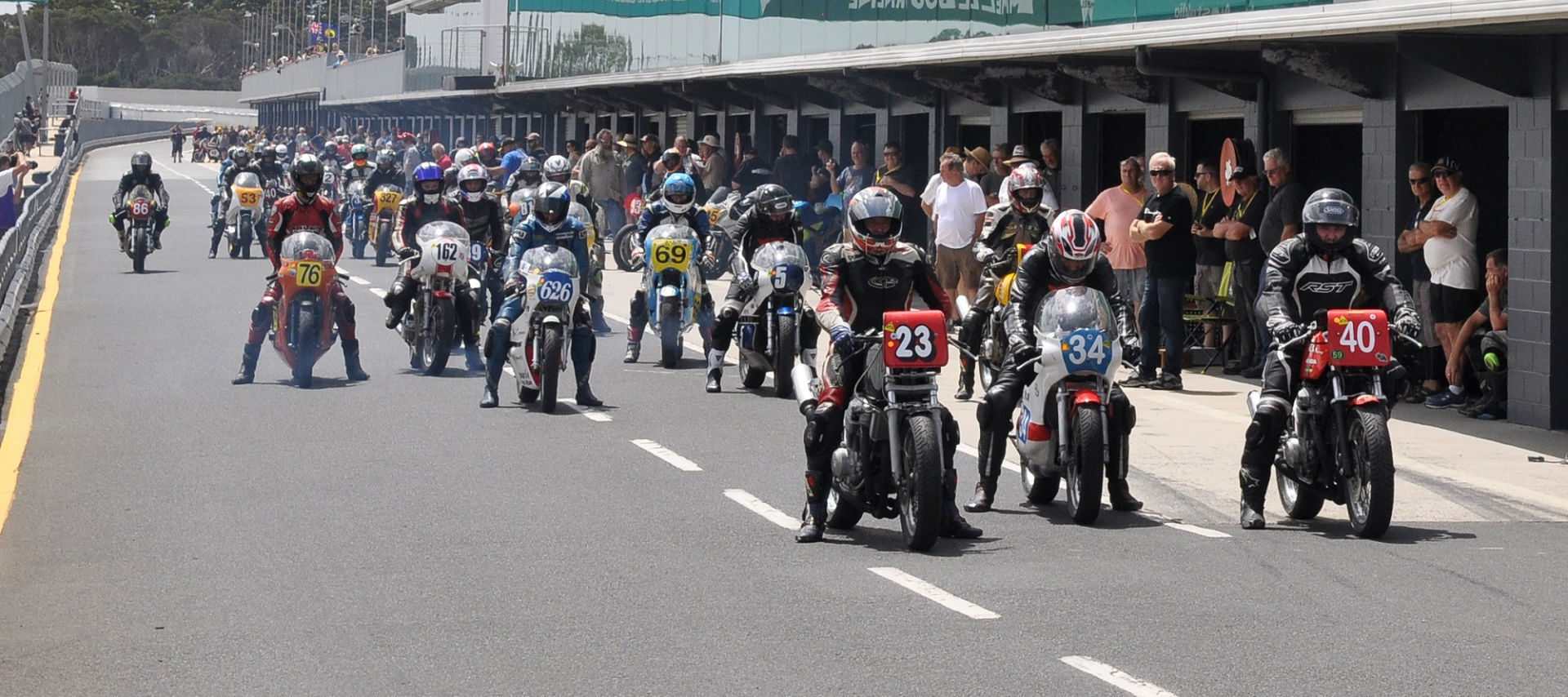 Vintage motorcycles on pit lane at Phillip Island during a past International Island Classic event. Photo courtesy of Phillip Island Grand Prix Circuit.