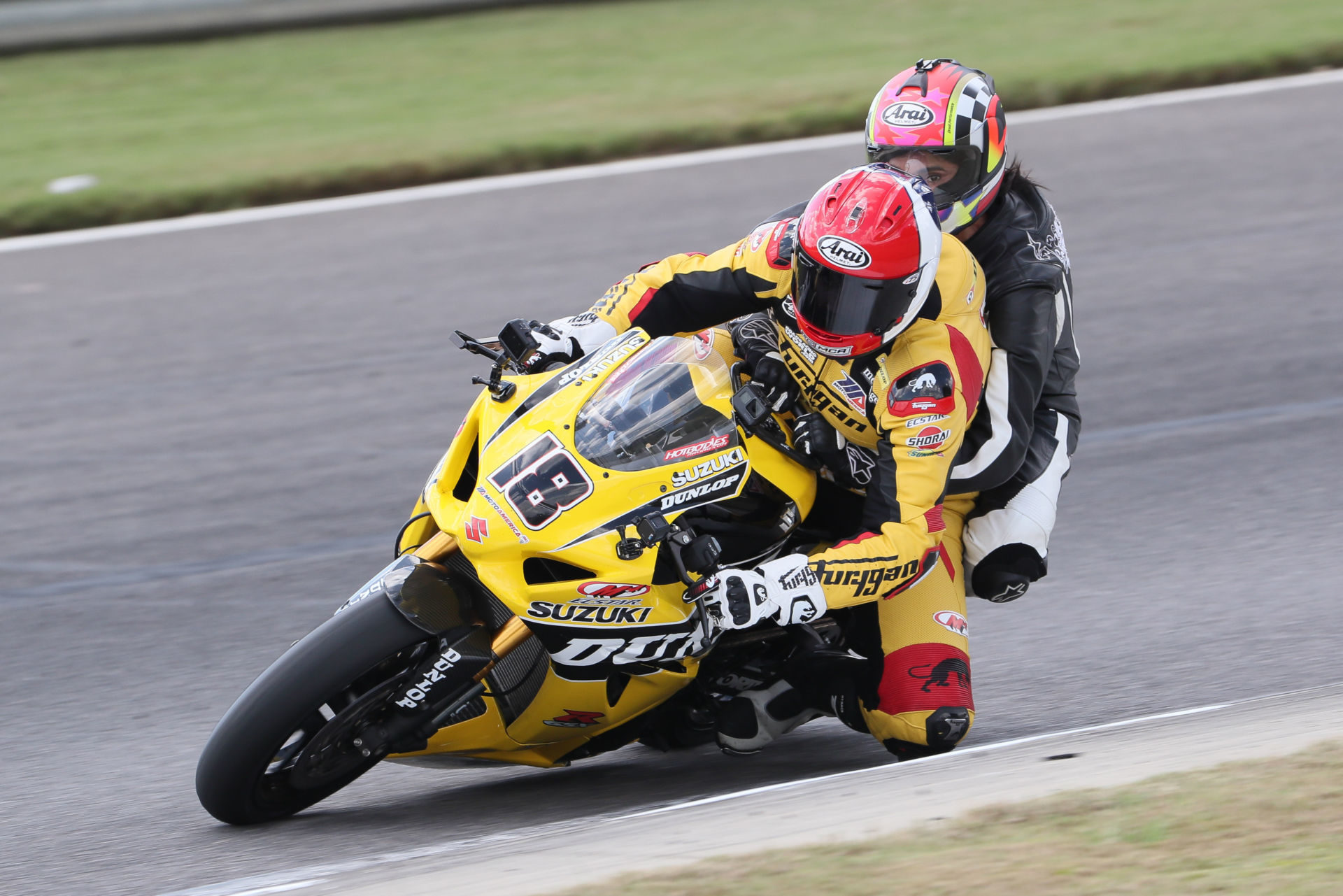 Chris Ulrich (18) giving a ride on his two-seat Dunlop M4 Suzuki GSX-R1000R Superbike at a MotoAmerica event. Photo by Brian J. Nelson.