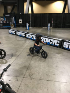 A determined little kid on an electric STACYC 12eDrive on a demo course at the IMS show in Long Beach, California. Photo by John Ulrich.