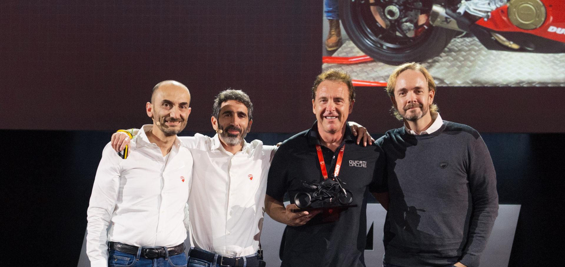 Ducati CEO Claudio Domenicali (far left), Ducati VP Global Sales & After Sales Director Francesco Milicia (second from left), AMS Ducati Dallas Founder and President Jeff Nash (second from right), and Ducati North America CEO Jason Chinnock (far right) on stage at the Ducati Global Dealer Conference in Rimini, Italy. Photo courtesy of Ducati North America.