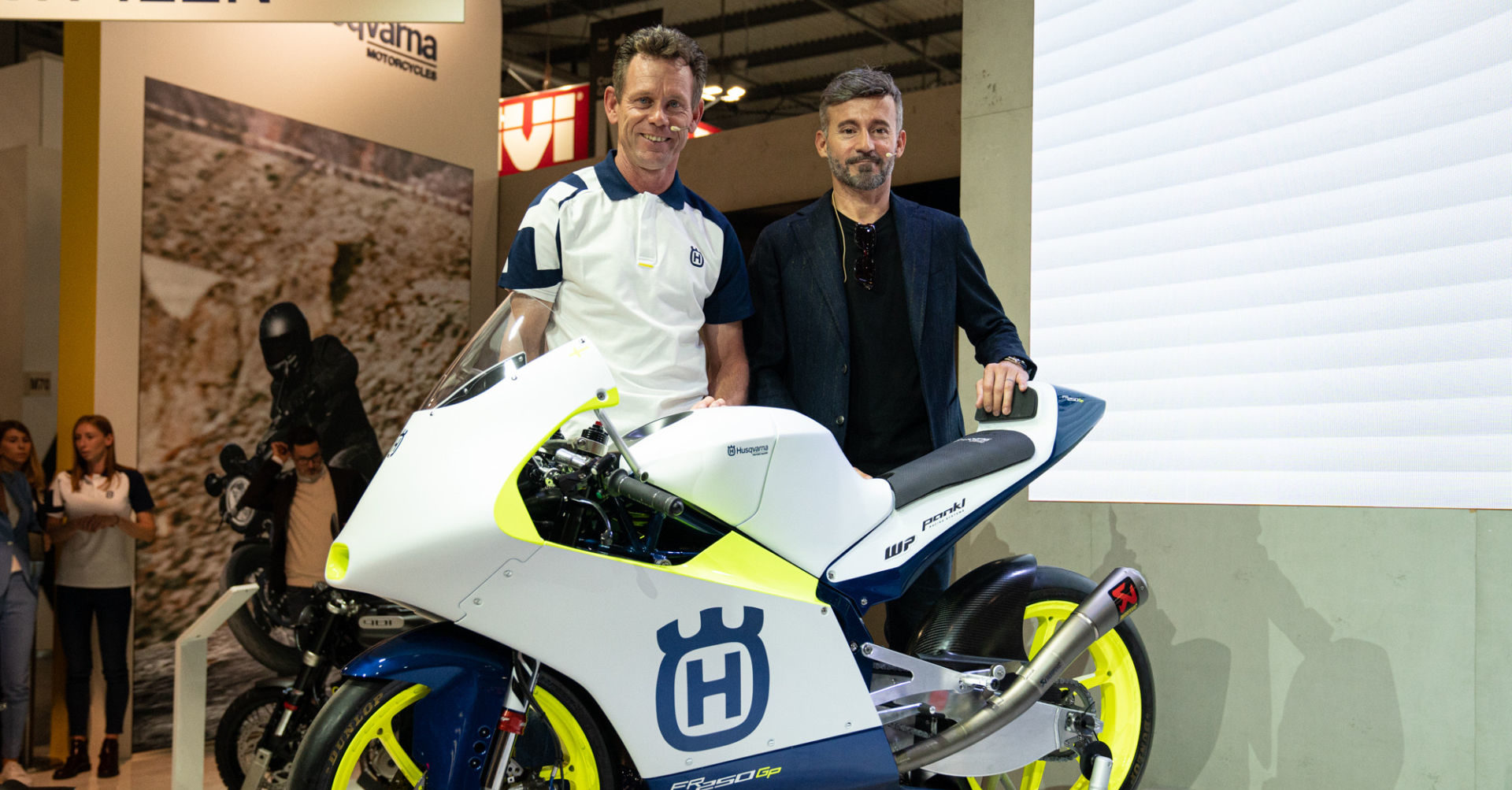 Max Racing Team Manager Peter Öttl (left), Max Racing Team Principal Max Biaggi (right), and a Husqvarna FR 250 GP Moto3 racebike. Photo courtesy of Husqvarna Motorcycles.