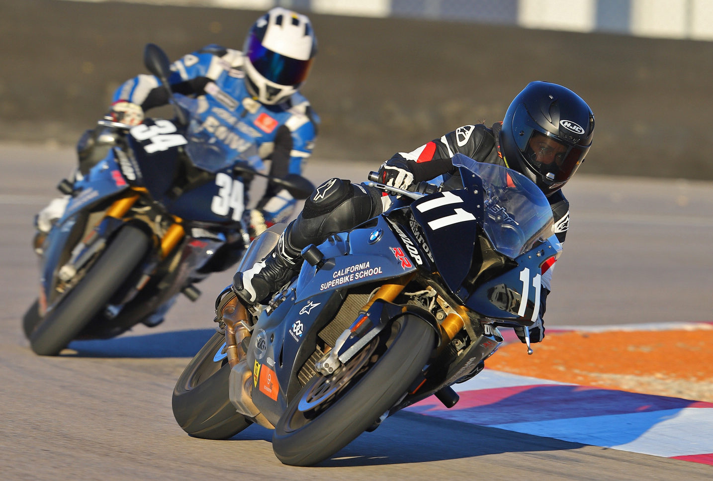 A California Superbike School instructor (34) follows a student (11) on track. Photo by etechphoto.com, courtesy of California Superbike School.