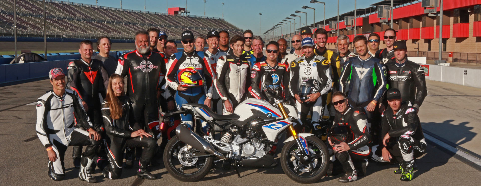 Fastrack Academy V coaches Chris Ulrich, Eric Bostrom, Jake Zemke and Josh Hayes (subbing for Jeremy Toye) and participants with the grand prize, a BMW G 310 R, at Auto Club Speedway. Photo by CaliPhotography.com, courtesy of Fastrack Academy.