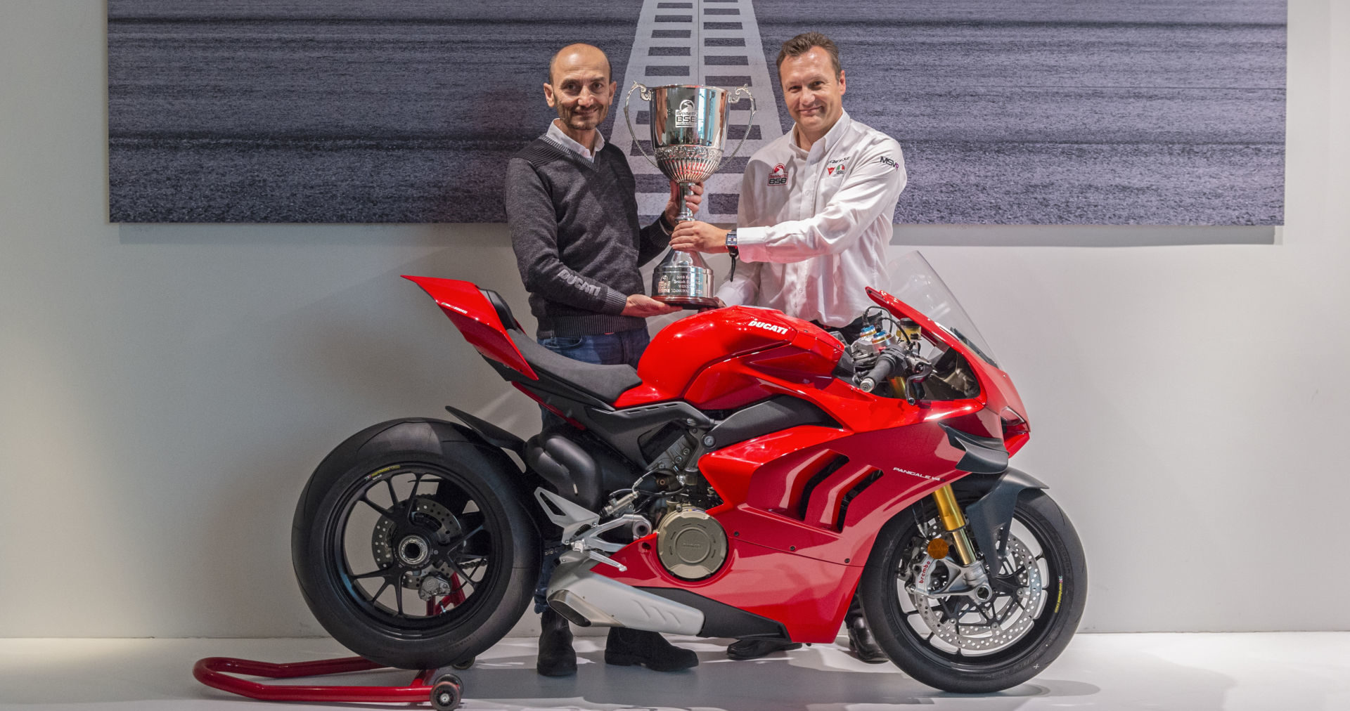 Ducati CEO Claudio Domenicali (left) accepting the British Superbike (BSB) Manufacturer Championship trophy from BSB Series Director Stuart Higgs (right) at Ducati's headquarters in Bologna, Italy. Photo courtesy of Ducati.