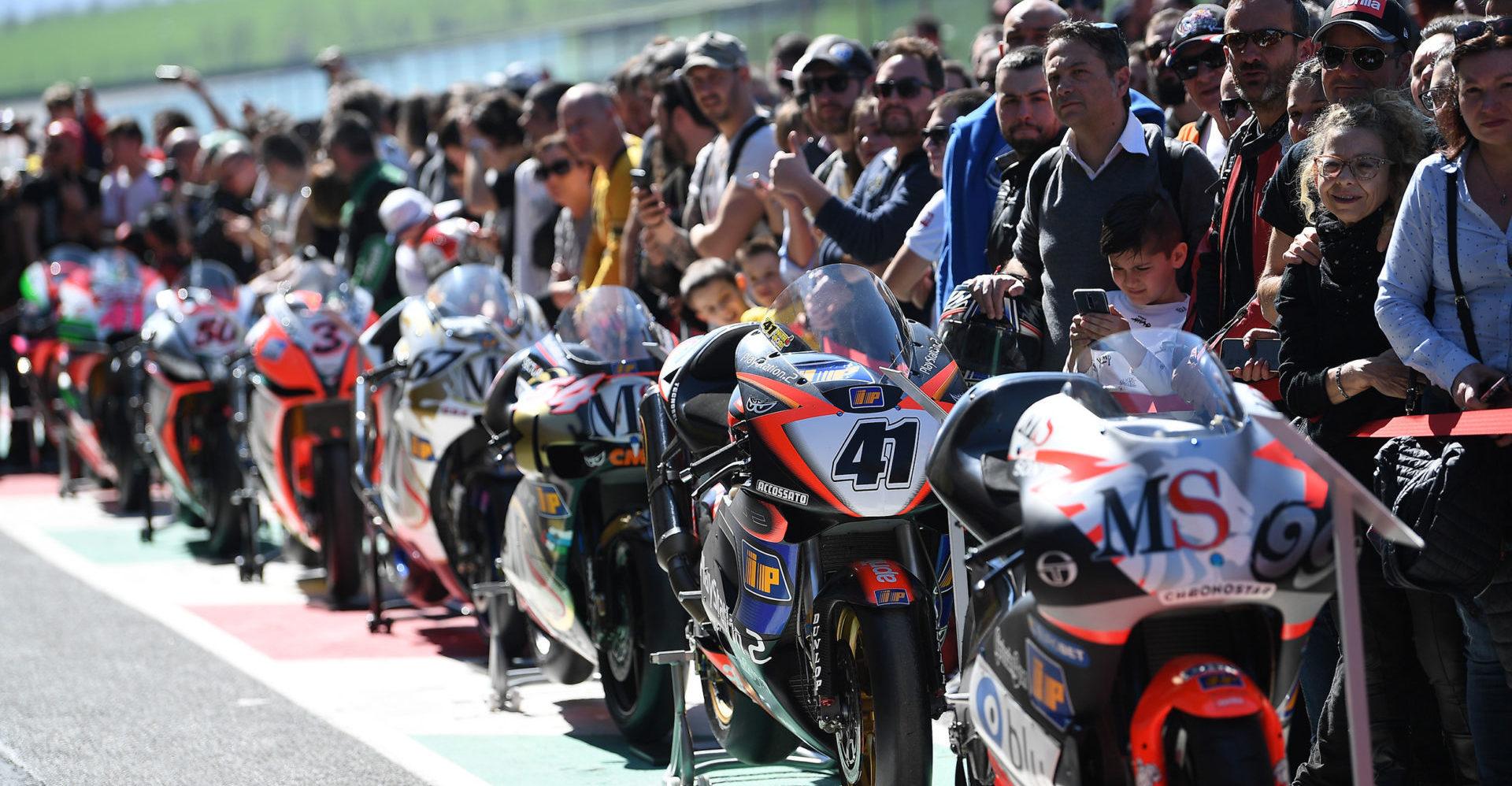 Fans and retired Aprilia racebikes lined up at Aprilia All Stars in 2019. Photo courtesy of Aprilia.