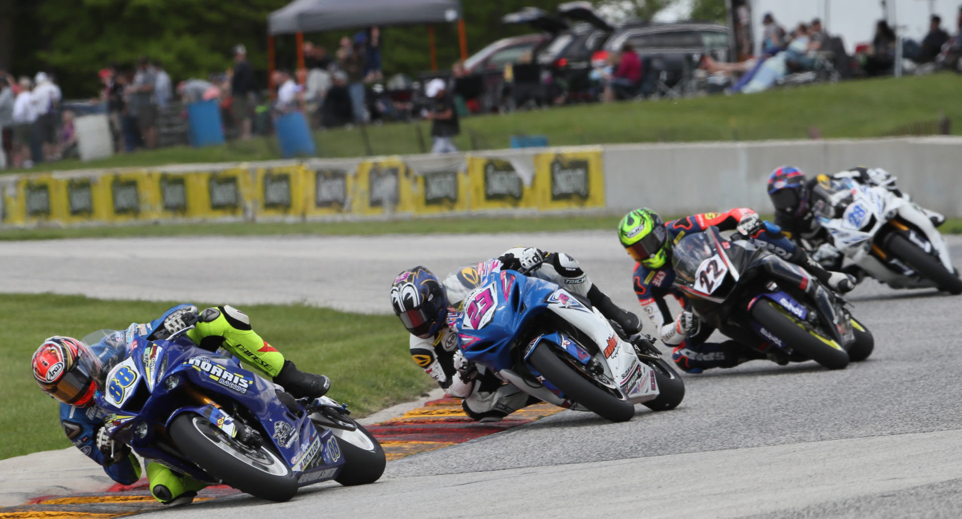 MotoAmerica Supersport competitors Benjamin Smith (88), Lucas Silva (23), Ashton Yates (22), and Cory Ventura (28) racing in front of fans at Road America in 2019. Photo by Brian J. Nelson.