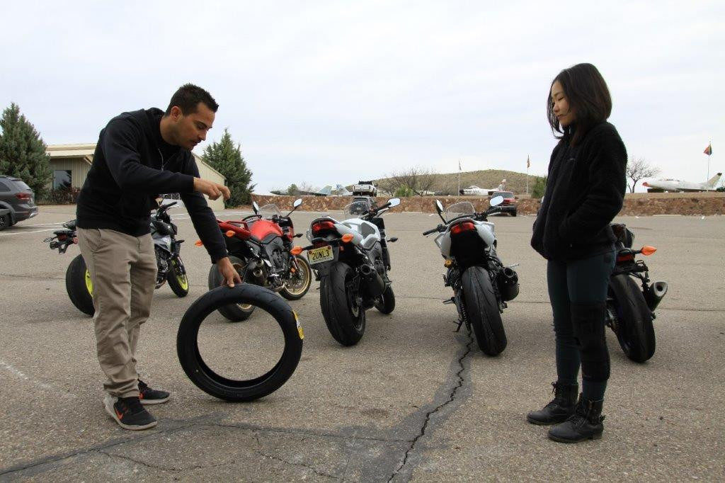 Yamaha Champions Riding School instructor and Army of Darkness rider Chris Peris (left) explains to Hiyori Yoshida how trail-braking, or turning, loads the front tire and increases the contact patch.