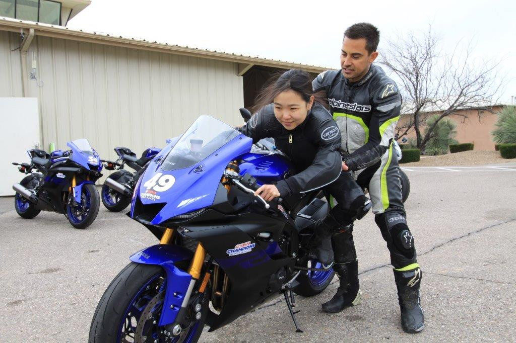 Yamaha Champions Riding School instructor and Army of Darkness rider Chris Peris teaching Hiyori Yoshida proper sportbike riding body positioning. After years of learning to be positioned on the high side of the seat for dirt riding, it was a bit of an adjustment to be on the low side of the seat.