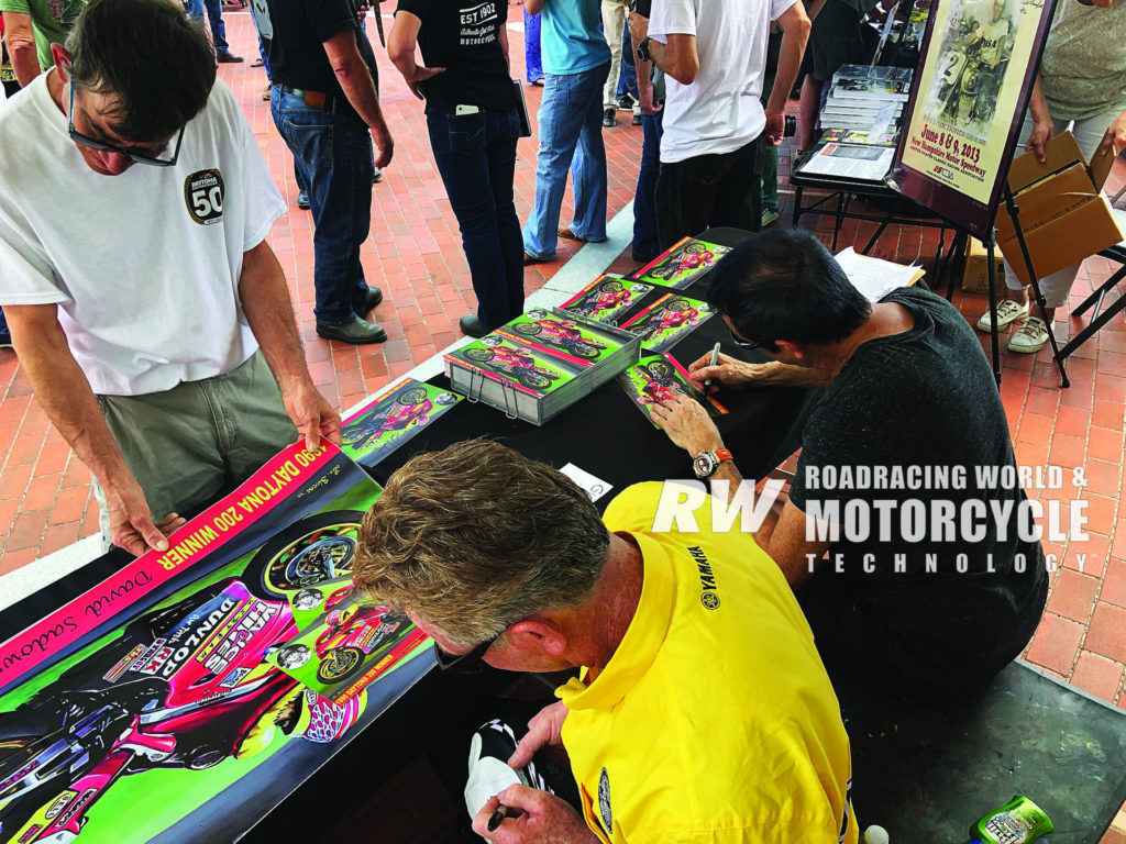 Artist Lee Bivens (right) and previous Daytona 200 race winner David Sadowski (left) signed autographs on small, free hero cards and sold full-size prints of Bivens' painting of Sadowski to help raise funds for the Daytona 200 Monument Fund. Photo by Bob Coy.