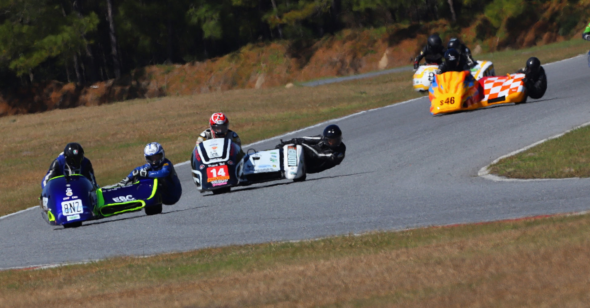 AHRMA sidecar racers Tony Doukas/Lisa Doukas (8NZ), Peter Essaff/Johnny Crown (14), Dale Lavendar/Hunter Longshore (46), and Nick Bailey/Adam Cramer (9) in action in 2020 at Roebling Road Raceway. Photo by etechphoto.com, courtesy AHRMA.