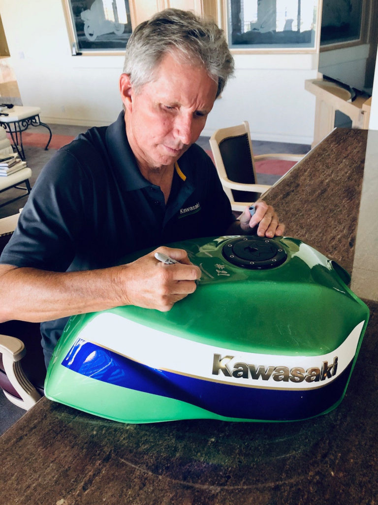 Four-time 500cc Grand Prix World Champion Eddie Lawson autographing the fuel tank of the 1999 Kawasaki ZRX1100 tribute bike being raffled by AHRMA. Photo courtesy AHRMA.