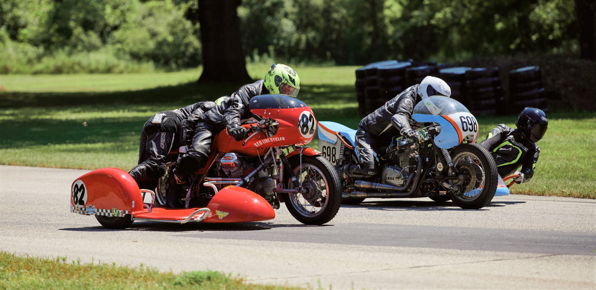 Eric Trosper and passenger Celia Trosper, riding their Loud Valve Racing Moto Guzzi, (X82) and Brad Carlisle and passenger Eddie Neubauer, riding their Sniper Monkey Racing Yamaha, (698) race into Blackhawk Farm Raceway's Turn Five. Photo by Daniel Peter, courtesy AHRMA.