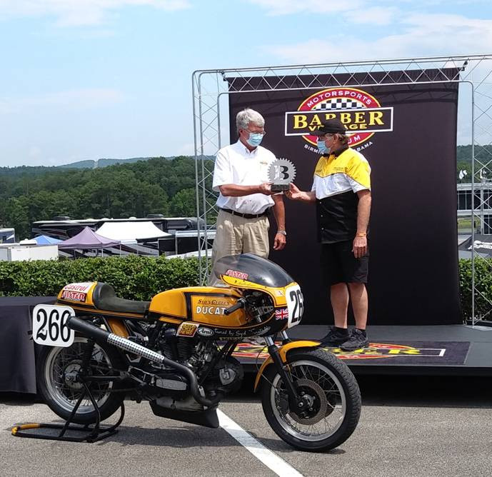 Barber Motorsports Park's George Barber hands Malcome Tunstall the first-place trophy in the