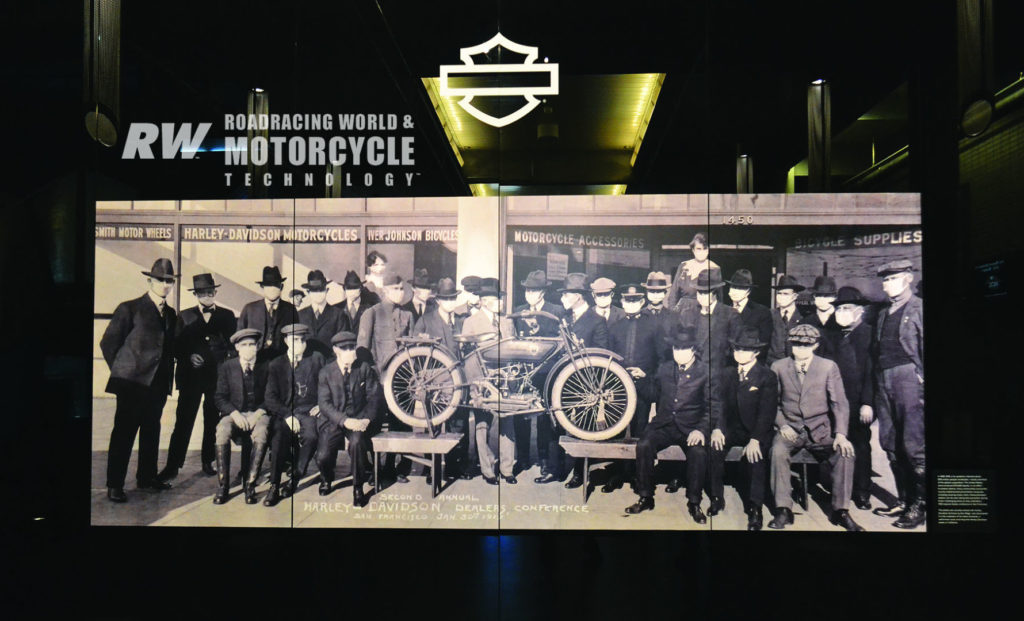 At the Harley-Davidson Museum near Milwaukee, a photo in the reception hall, sourced from a private collector, shows attendees at the 1919 Harley-Davidson dealer show wearing face masks due to the Spanish Flu pandemic.