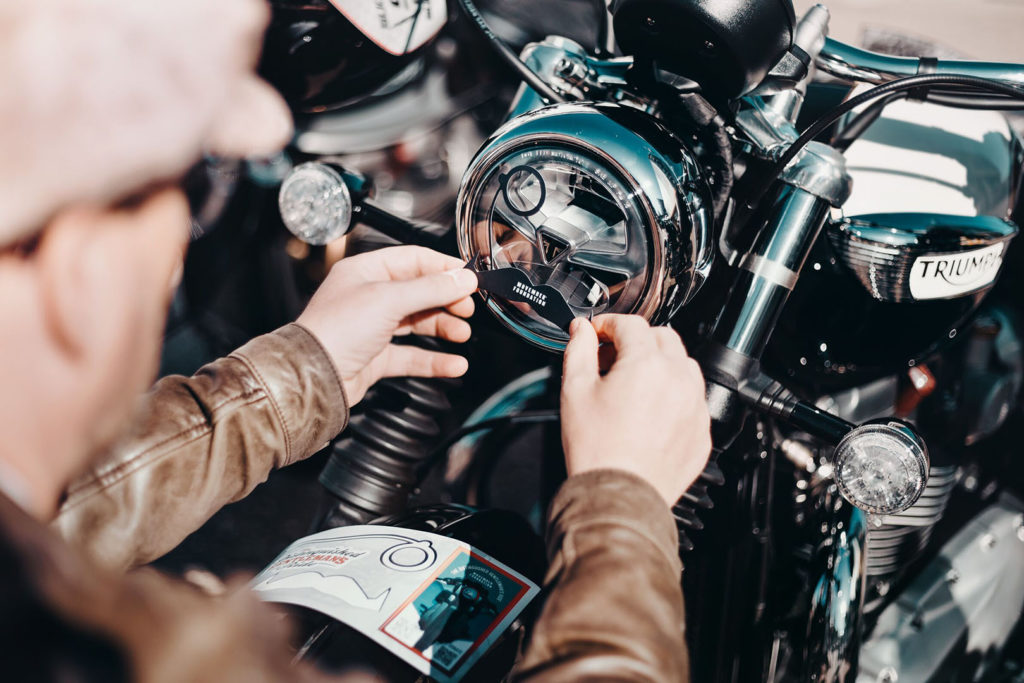 A participant putting a DGR decal on the headlight of his motorcycle. Photo courtesy Triumph.