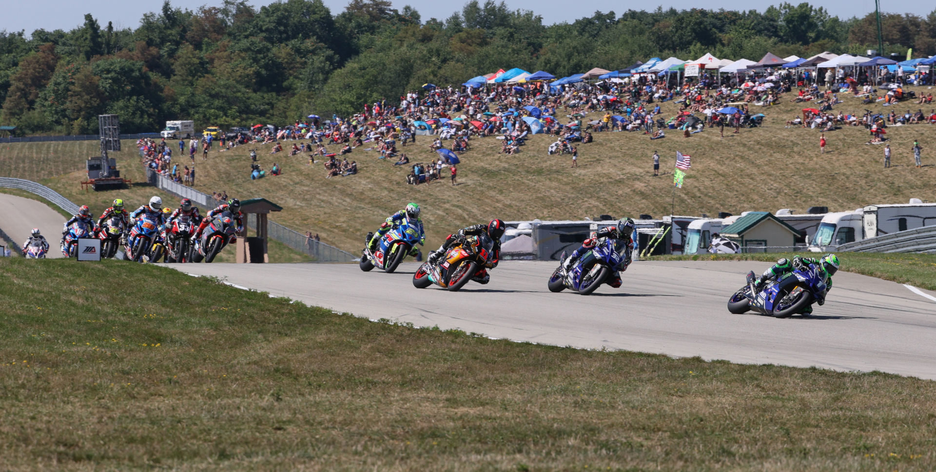 Cameron Beaubier (1) leads Jake Gagne (32), Mathew Scholtz (11), Toni Elias (24) and the rest of the field at the start of MotoAmerica HONOS Superbike Race Two at PittRace. Photo by Brian J. Nelson, courtesy MotoAmerica.