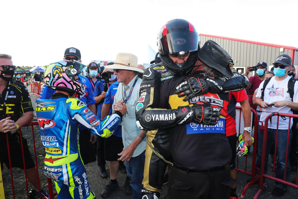 Rider Mathew Scholtz hugs Westby Racing team owner Tryg Westby after finishing second in the Saturday Superbike race. Photo by Brian J. Nelson.