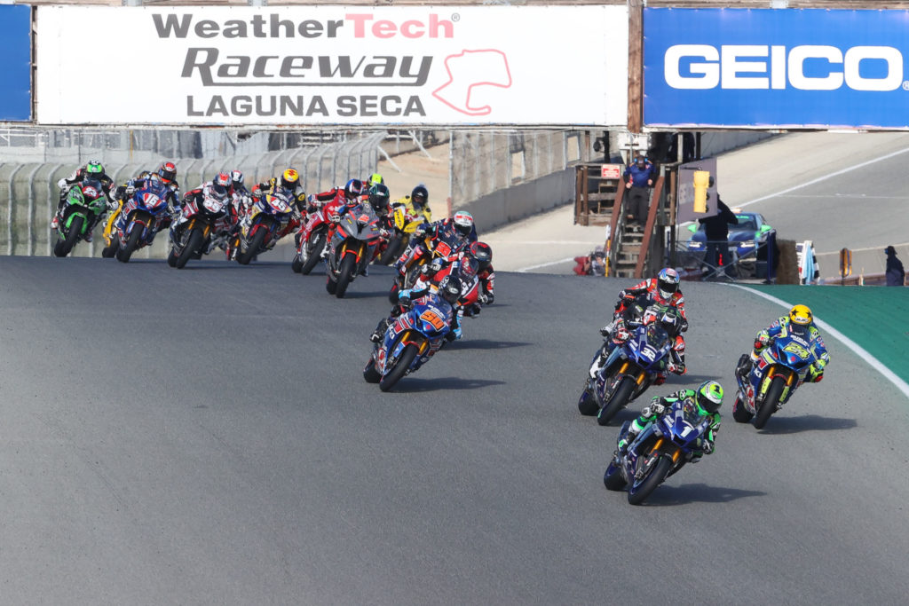 Cameron Beaubier (1) leads Toni Elias (24), Jake Gage (32), Lorenzo Zanetti (behind Gagne), Bobby Fong (50), Kyle Wyman (behind Fong), Niccolo Canepa (behind Wyman), Josh Herrin (2), and the rest of the HONOS Superbike field during a race start Sunday at Laguna Seca. Photo by Brian J. Nelson, courtesy MotoAmerica.