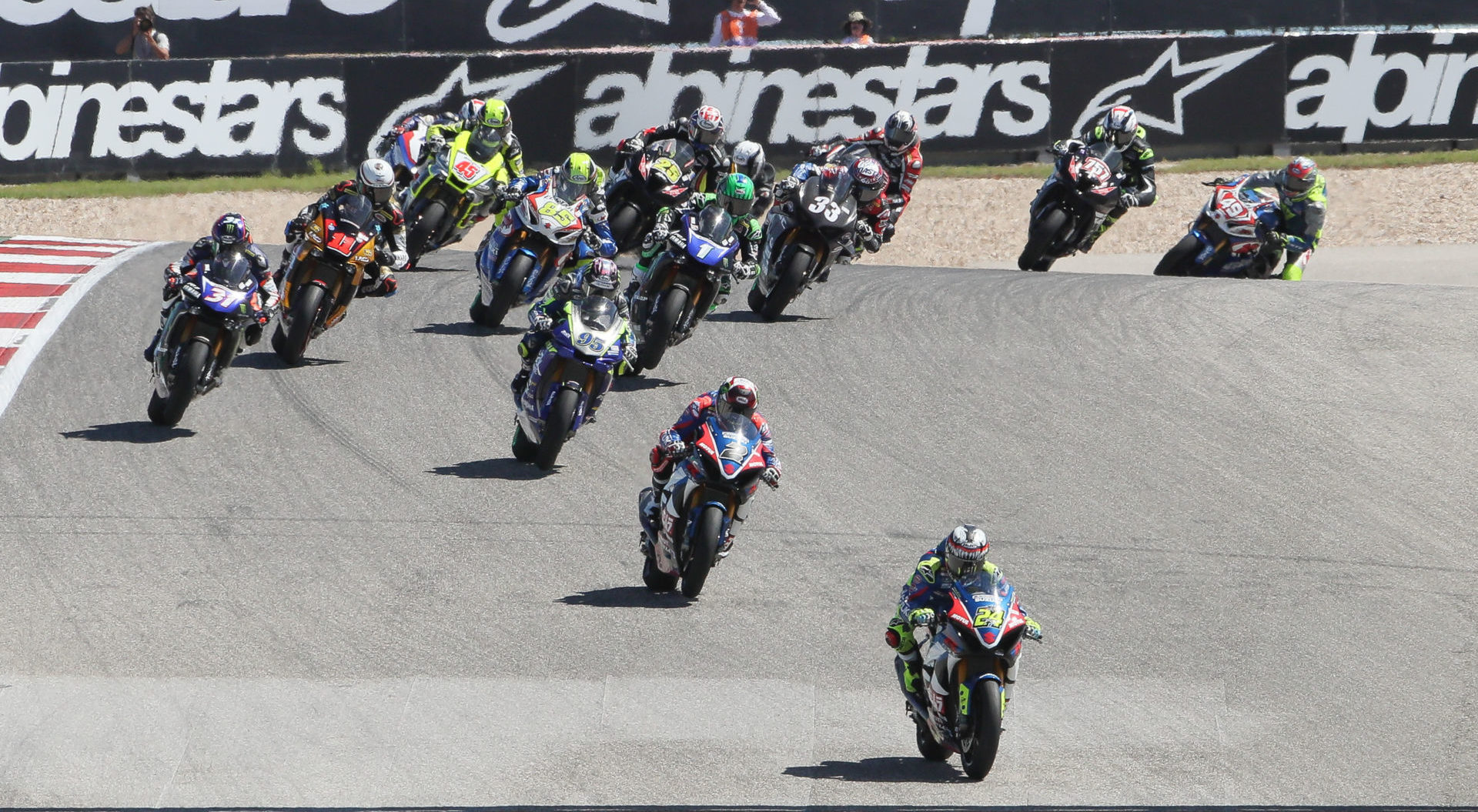 The start of a MotoAmerica Superbike race at COTA in 2019 with Toni Elias (24) leading Josh Herrin (2), JD Beach (95), Garrett Gerloff (31), Mathew Scholtz (11), Cameron Petersen (45), Jake Lewis (85), Cameron Beaubier (1), David Anthony (25), Kyle Wyman (33) and the rest of the field out of Turn One. Photo by Brian J. Nelson.