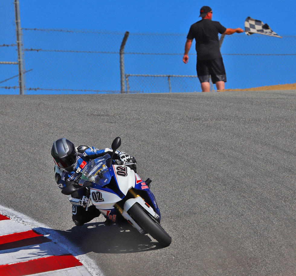 A California Superbike School instructor takes the checkered flag at the Corkscrew at Laguna Seca. Photo by etechphoto.com, courtesy California Superbike School.