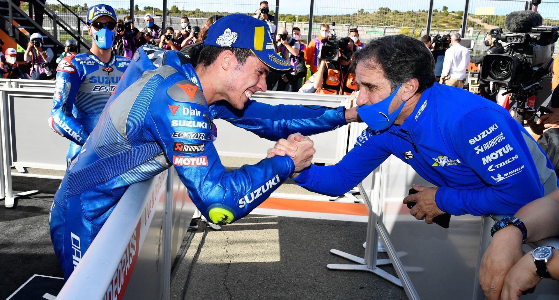 Davide Brivio (right) shakes hands with 2020 MotoGP World Champion Joan Mir (left). Mir's teammate Alex Rins looks on in the background. Photo courtesy Team Suzuki Press Office.