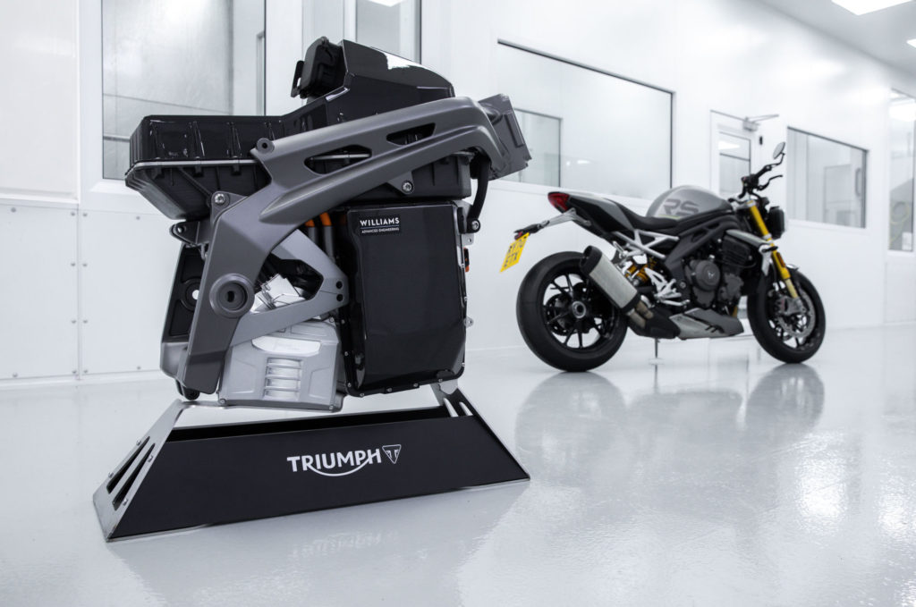 A Triumph TE-1 electric powertrain and battery pack mounted in a prototype frame with a 2021 Triumph Speed Triple 1200 RS in the background. Photo courtesy Triumph.