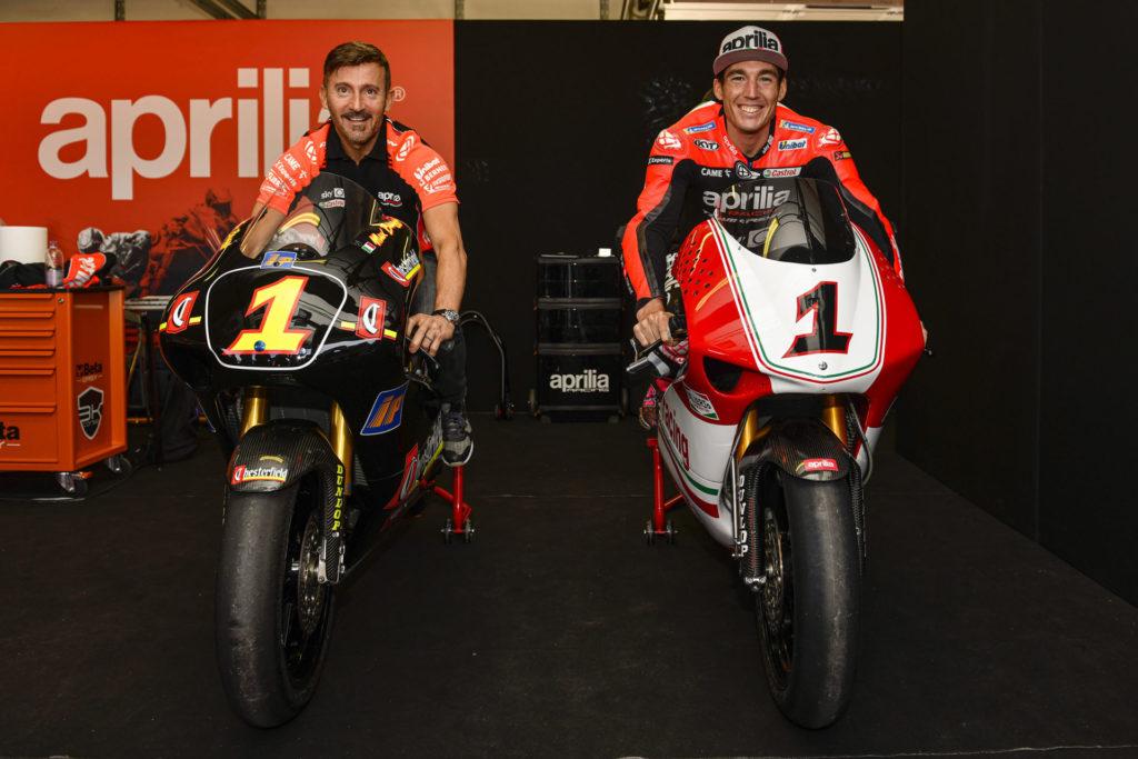 Max Biaggi (left) and Aleix Espargaro (right) seated on Biaggi's World Championship-winning Aprilia 250s at Misano. Photo courtesy Aprilia.
