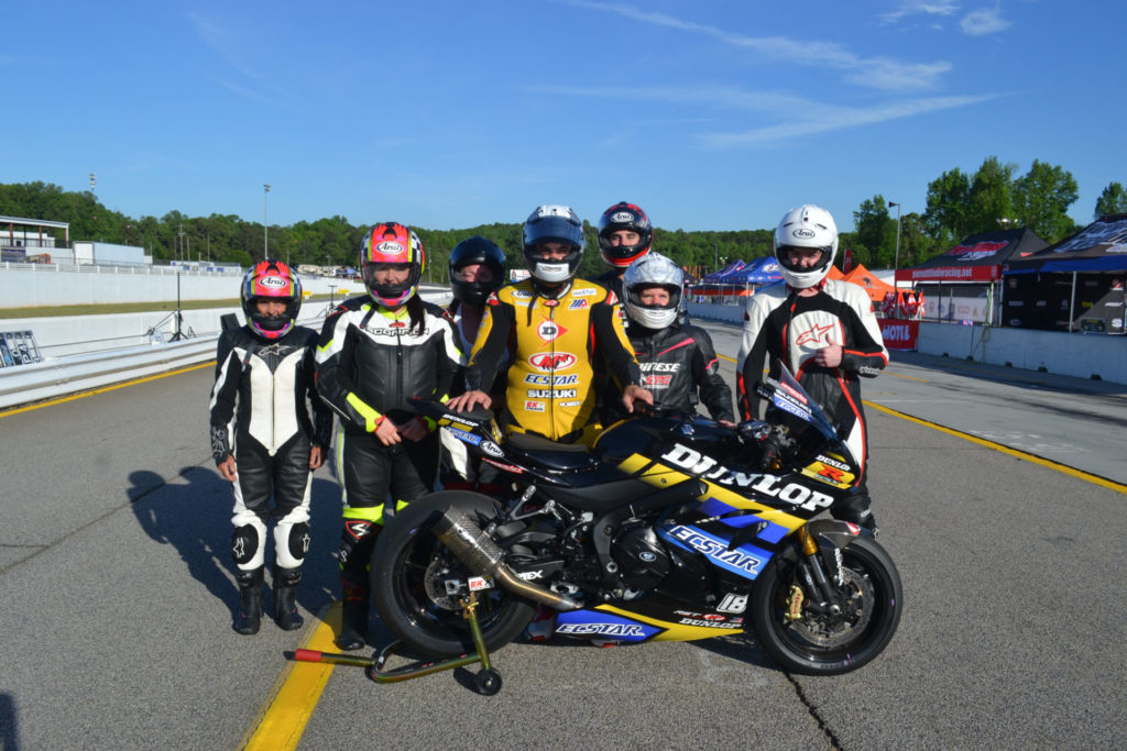 Chris Ulrich (center) poses with a group of passengers after giving rides on the Dunlop ECSTAR Two-Seat Superbike. ECSTAR is co-title sponsor of the program in 2021. Photo courtesy Team Hammer.