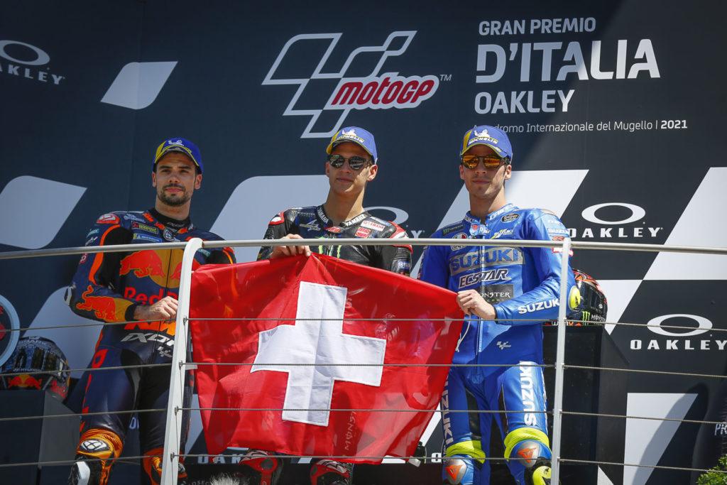 MotoGP race winner Fabio Quartararo (center), runner-up Miguel Oliveira (left), and third-place finisher Joan Mir (right) on the podium holding a Swiss flag in honor of fallen Moto3 racer Jason Dupasquier. Photo courtesy Dorna.