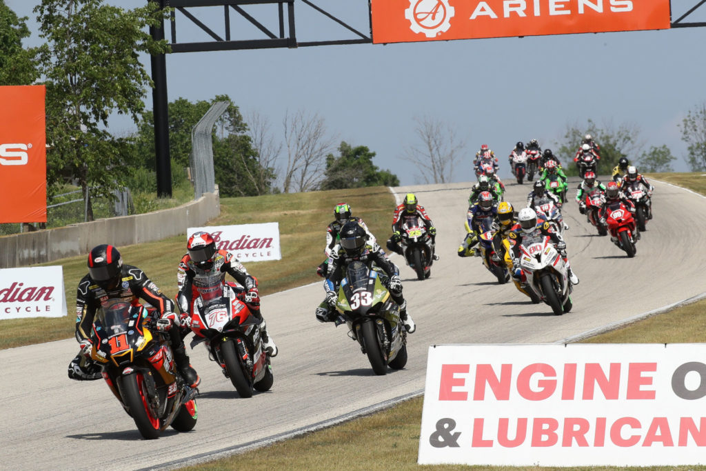 Matthew Scholtz (11) leads a group of riders during MotoAmerica Superbike Race One. Photo by Brian J. Nelson, courtesy Westby Racing.