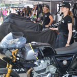 Royal Enfield Build Train Race (BTR) road race participants Scarlett Grosselangehorst (right) and Trisha Dahl (left) with their Royal Enfield Continental GT 650 racebike builds under covers. BTR program mentor Melissa Paris' Royal Enfield racebike is in the foreground. Photo by David Swarts.