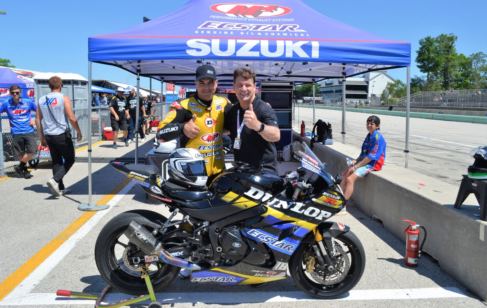 Ford President and CEO Jim Farley (right) with former Superbike racer Chris Ulrich (left) after they rode together on the Dunlop ECSTAR Suzuki GSX-R1000R two-seat Superbike June 13 during the MotoAmerica event at Road America. Photo by David Swarts.