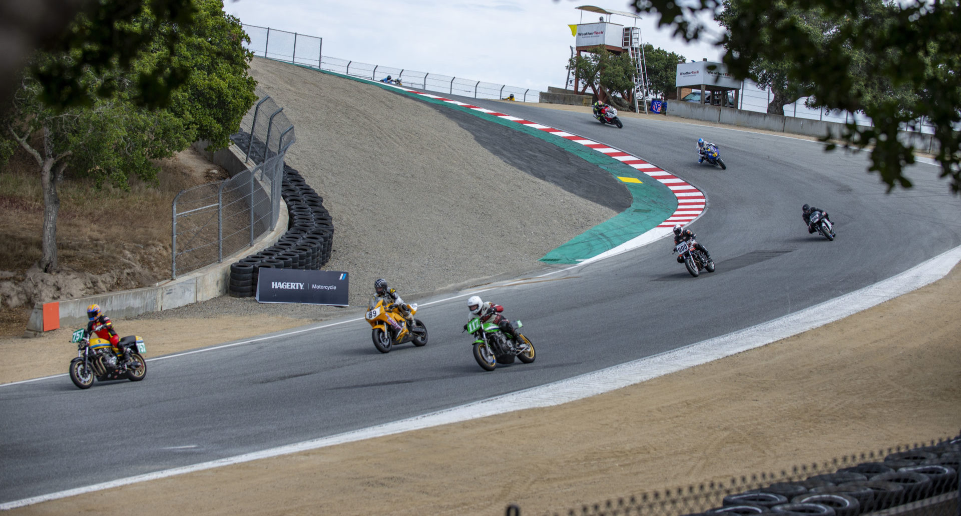 AHRMA racers Michael Butler (757), John Deuser (189), Dave Crussell (119), Mathew Morse (055), Mike Root (R66), Alex Spanos (L29), and Kevin McKee (900) in action at Laguna Seca. Photo by Kevin McIntosh, courtesy AHRMA.