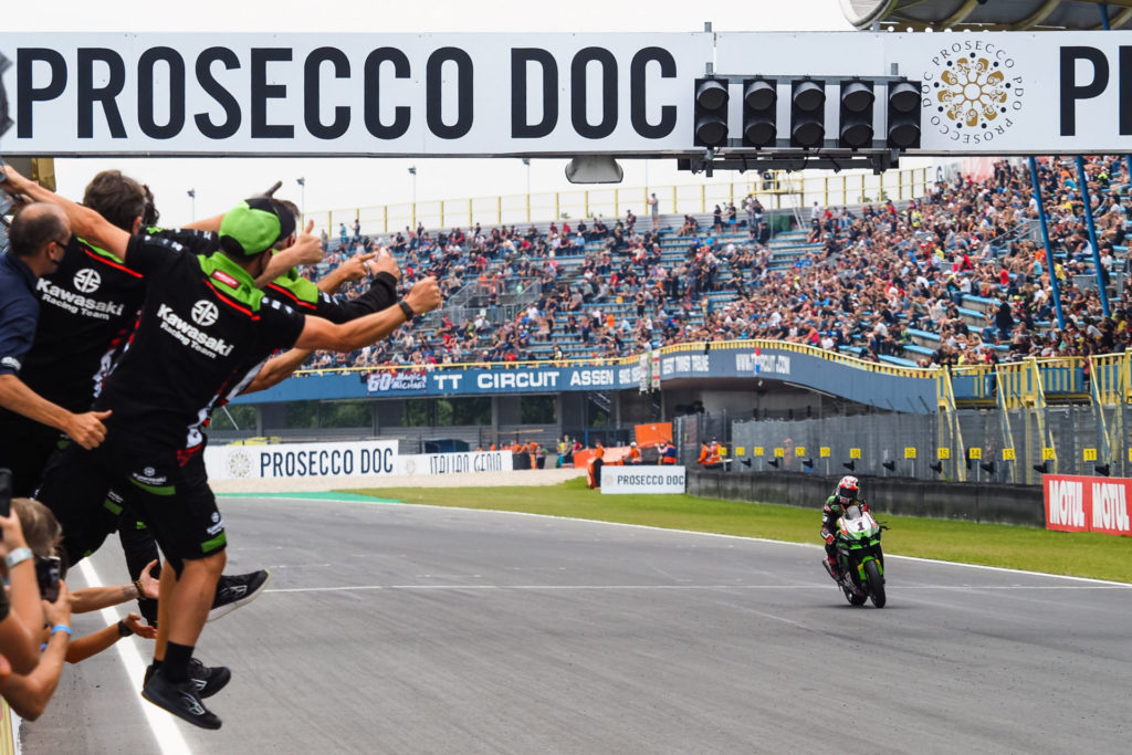 Jonathan Rea's (1) team greets him with cheers as he takes the checkered flag at Assen. Photo courtesy Dorna.