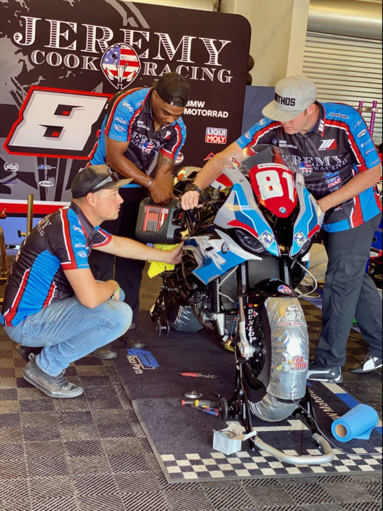 Jeremy Cook Racing VETM volunteers Patrick Corey (left), Alex Panetta (center) and team mechanic Dakari Harris (right) work to get the team's BMW S 1000 RR ready for the Stock 1000 race at Laguna Seca. Photo courtesy of Jeremy Cook Racing.