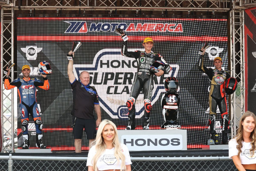 Superbike Race One winner Jake Gagne and his crew chief Jon Cornwall (center) flanked by runner-up Bobby Fong (left) and third-place finisher Mathew Scholtz (right) on the podium at Brainerd. Photo by Brian J. Nelson.