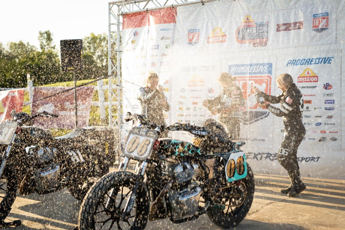 Jillian Deschenes (center), Jaycee Jones (left), and Malary Lee (right) enjoy a champagne shower on the New York Short Track AFT podium. Photo courtesy Royal Enfield North America.