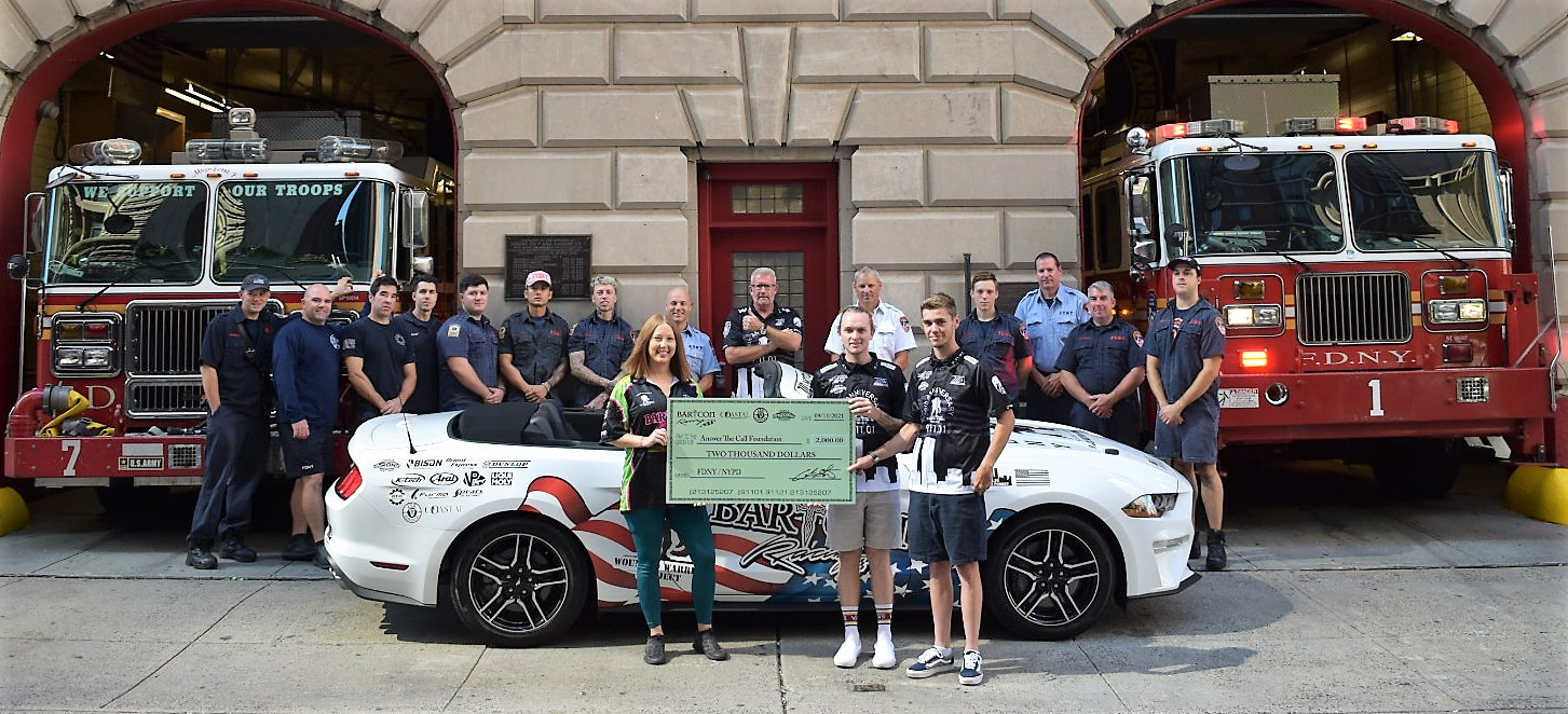 BARTCON Racing riders Dominic Doyle (front right), Anthony Mazziotto (second from right), and Tosha Lackey (front left) hold a $2,000 ceremonial check representing a donation to the Answer The Call foundation. BARTCON Racing owner Colin Barton is standing in the doorway directly behind the check. Photo by Robert Lackey, courtesy BARTCON Racing.