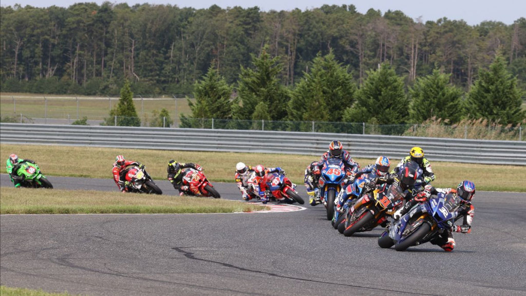 Jake Gagne (32) leads Mathew Scholtz (11), Bobby Fong (behind Scholtz), Cameron Petersen (45) and the rest of the field during a Superbike race Sunday at NJMP. Photo by Brian J. Nelson, courtesy MotoAmerica.