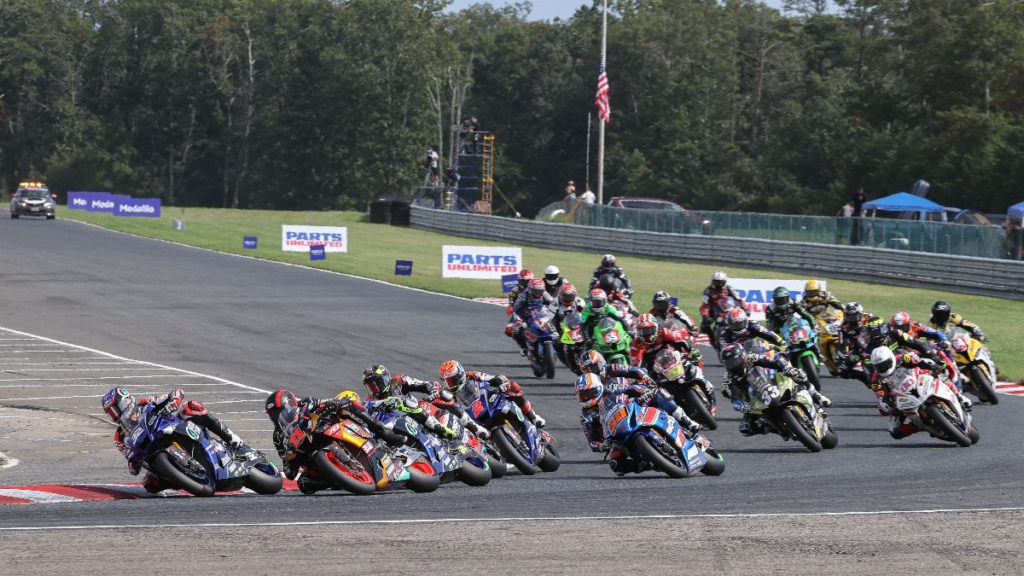 Jake Gagne (32) leads Mathew Scholtz (11), Toni Elias (behind Scholtz), Loris Baz (behind Elias), Josh Herrin (2), Bobby Fong (50), Cameron Petersen (behind Fong), Kyle Wyman (33), Hector Barbera (80) and the rest of the field at the start of Race One. Photo by Brian J. Nelson, courtesy MotoAmerica.