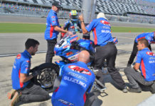 Sam Lochoff takes a quick drink while his M4 ECSTAR Suzuki crew refuels and installs new Dunlop tires on his GSX-R600 during his only pit stop. Photo by David Swarts.