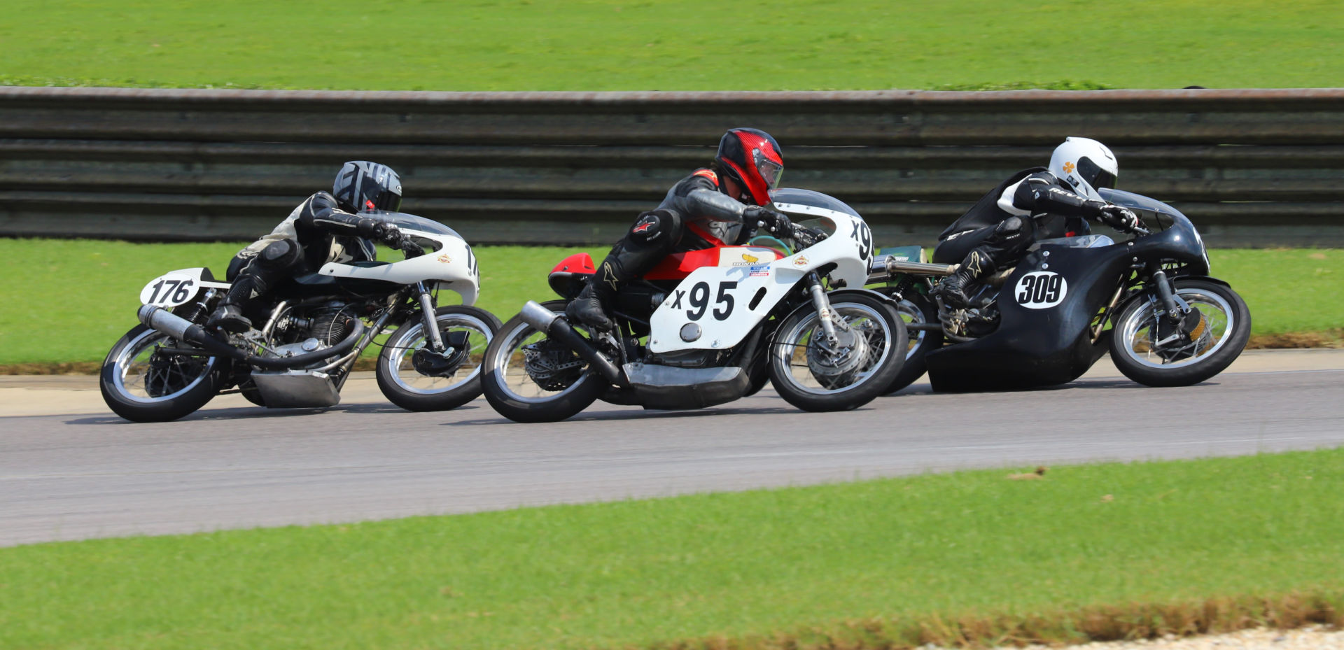 Tim Joyce (309), Andrew Mauk (x95), and Wes Orloff (176) battle during an AHRMA Vintage Cup race at Barber Motorsports Park. Photo by etechphoto.com, courtesy AHRMA.